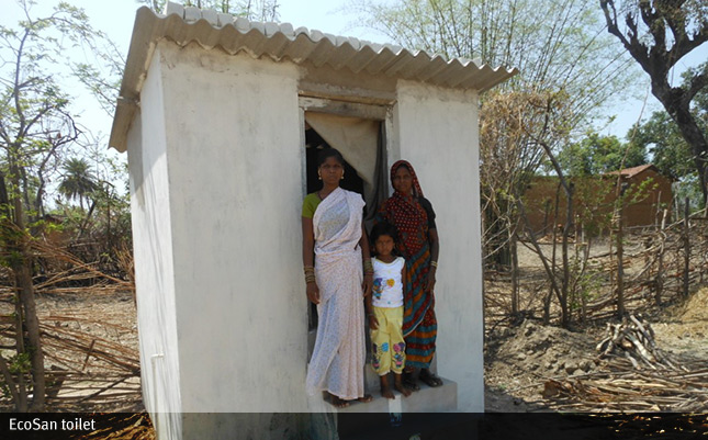 A photo of a family outside their EcoSan toilet in a village in India.