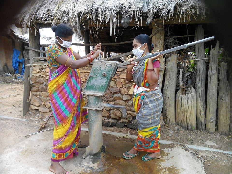 Two women wearing masks in a village in Odisha, India, fixing a water pump.