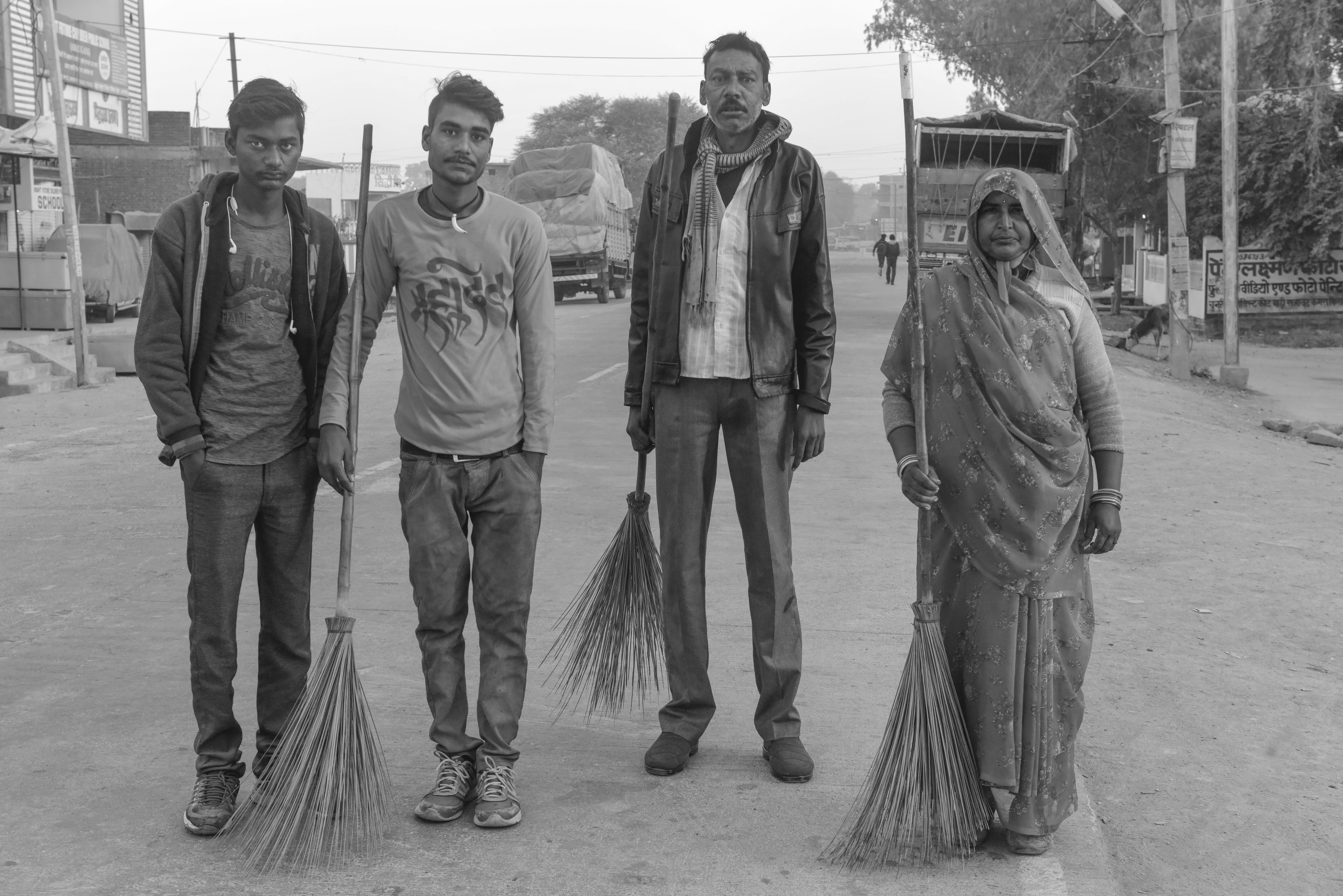 Four sanitation workers stand in the street. Santosh, third from left, suffered permanent eye damage after almost drowning emptying a pit latrine. His colleague died.