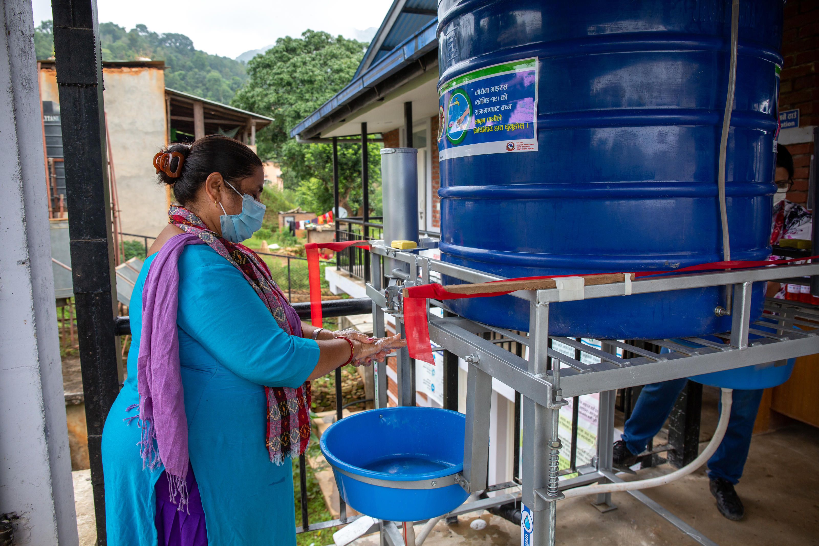 Sunita Kharel, senior auxiliary nurse midwife, Healthpost incharge, Bhumlutaar health post, washing her hands at a contactless handwashing station in Bhumlutaar, Kavre, Nepal, Sep 2020.