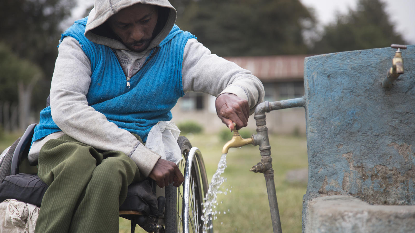 Wheelchair user collects water.
