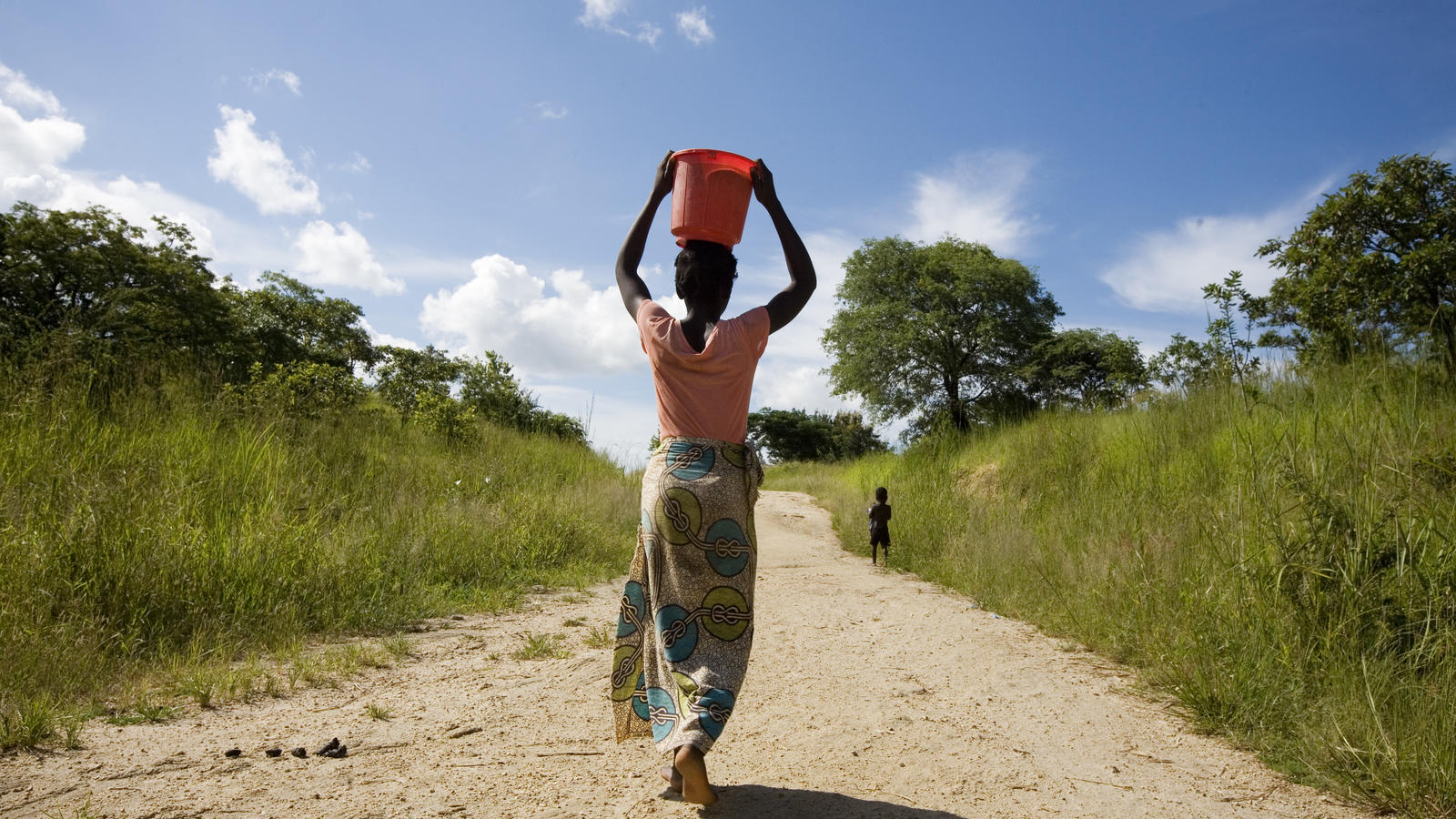 Mary, 22, carries the dirty water she has collected from the river, Malawi, March 2012.