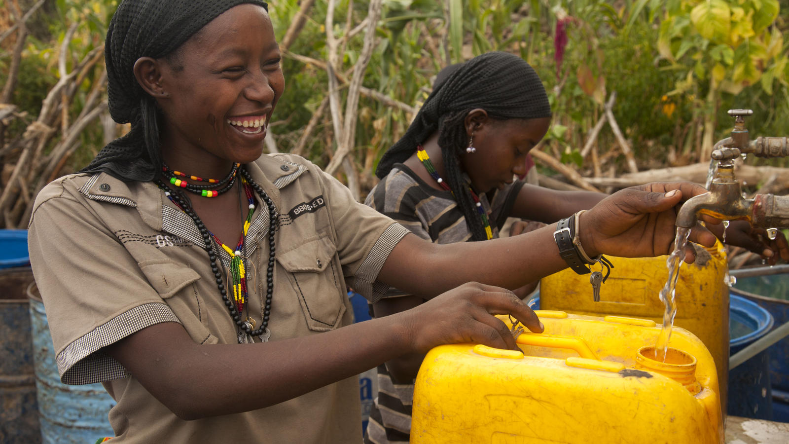 Kappa, smiles as she collects clean water from a tapstand, Aba Roba, Konso, Ethiopia, 2012.