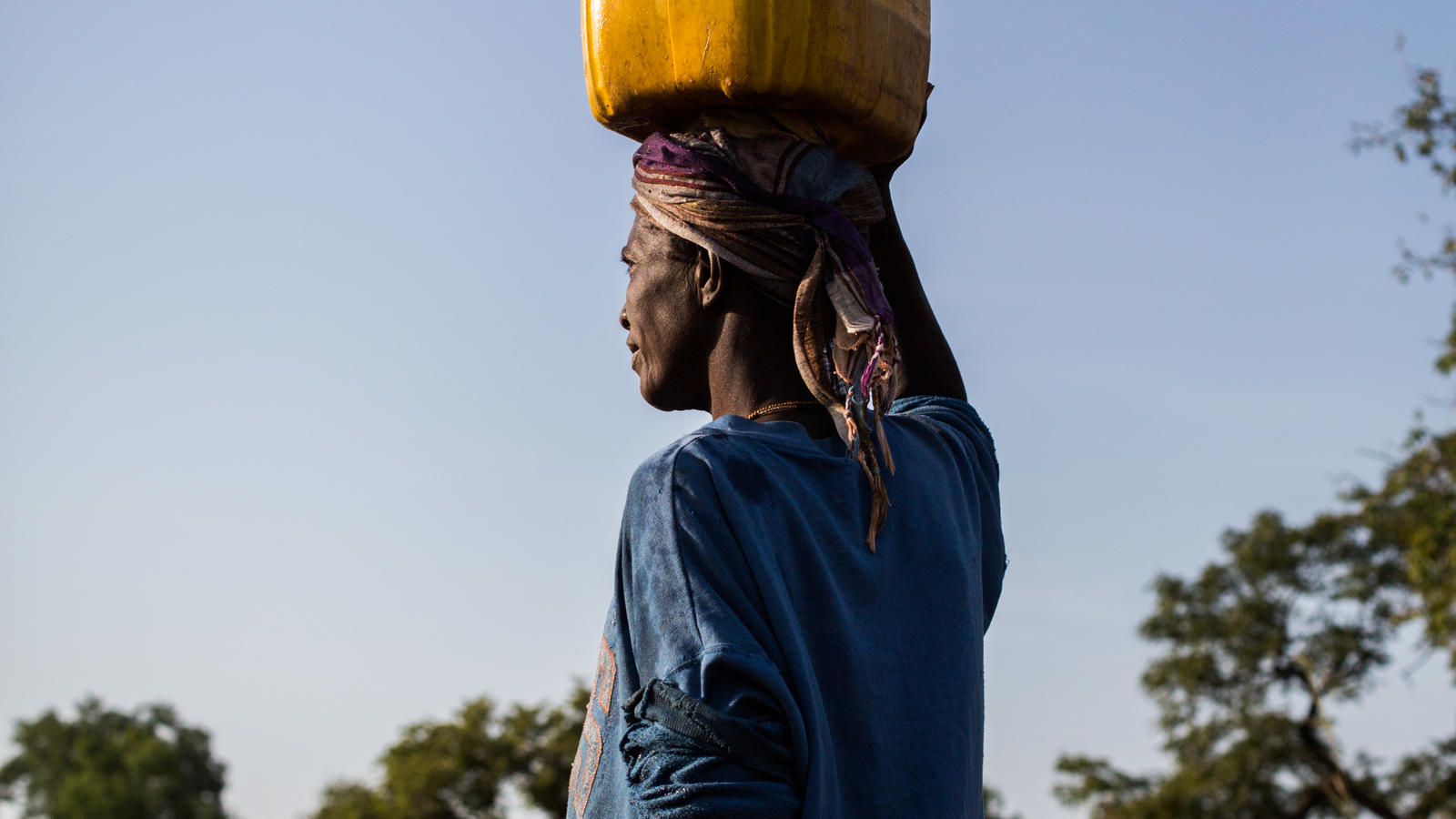 Bangre carries a jerry can in Imbina, Burkina Faso.