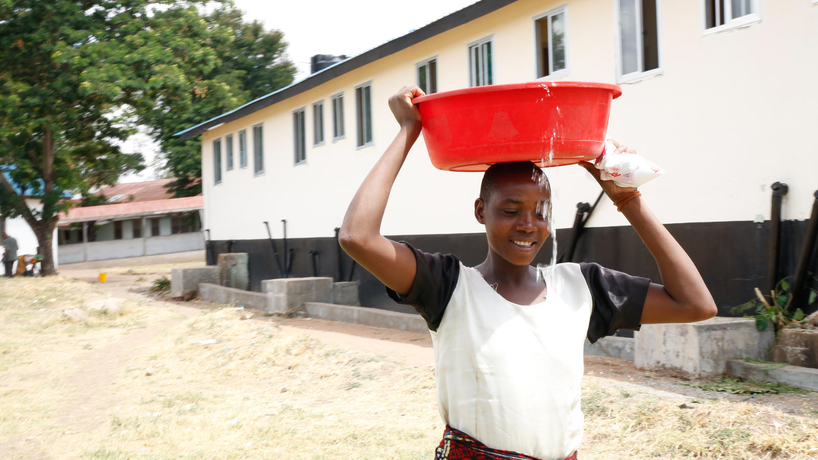 Dotto collects clean water at Kiomboi Hospital, Tanzania, which benefited from DfID match funding.