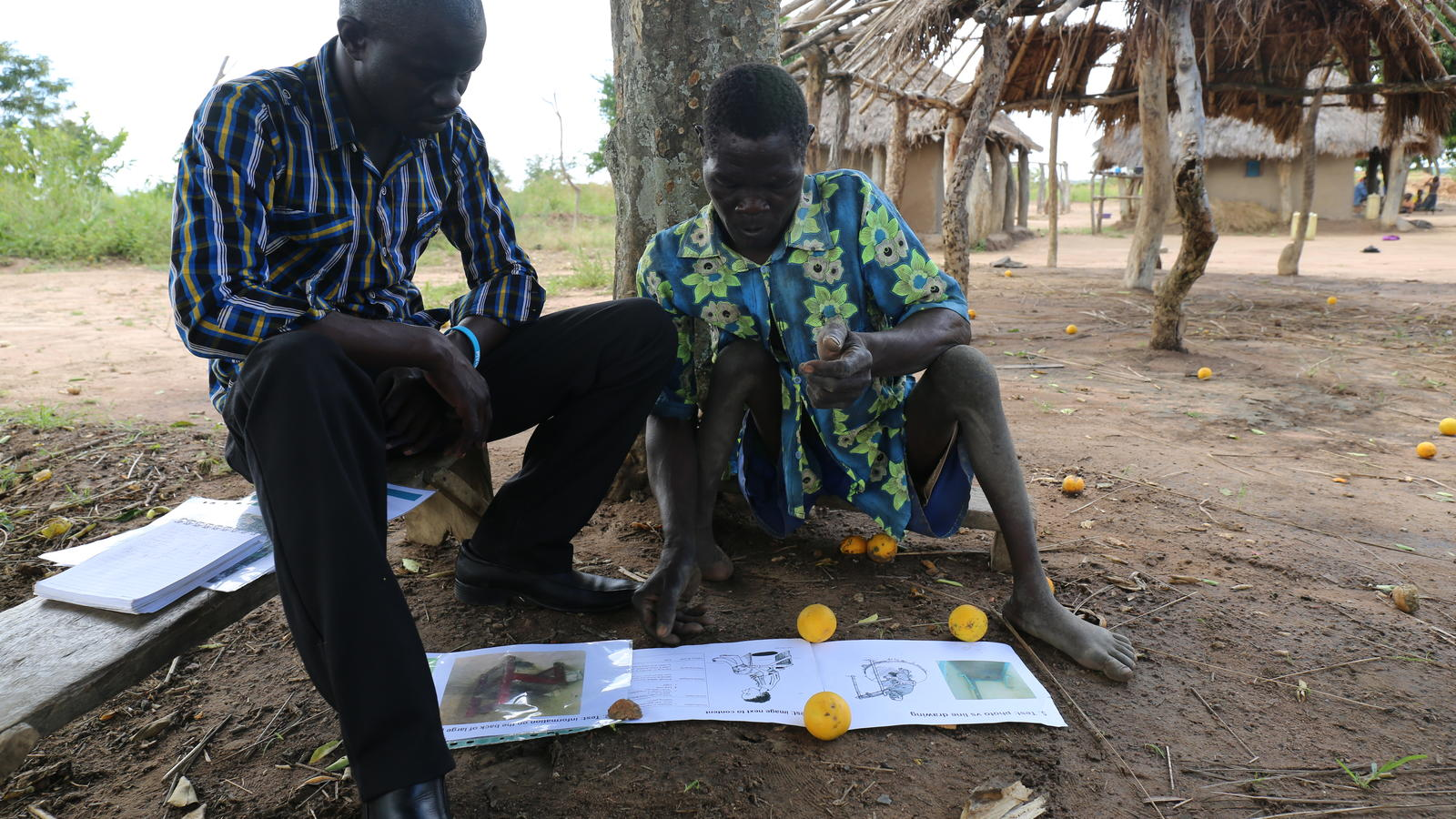 Olupot Martin, right, who has polio, works on inclusive water point designs in Abibico, Uganda