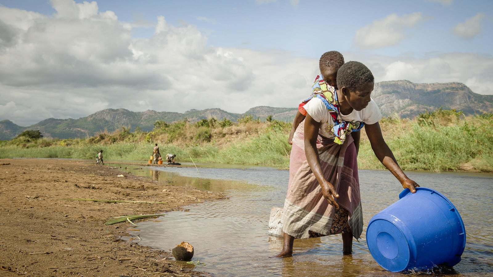 Helene carries her baby Agostinho on her back as she gathers water from the river near her village in Mozambique
