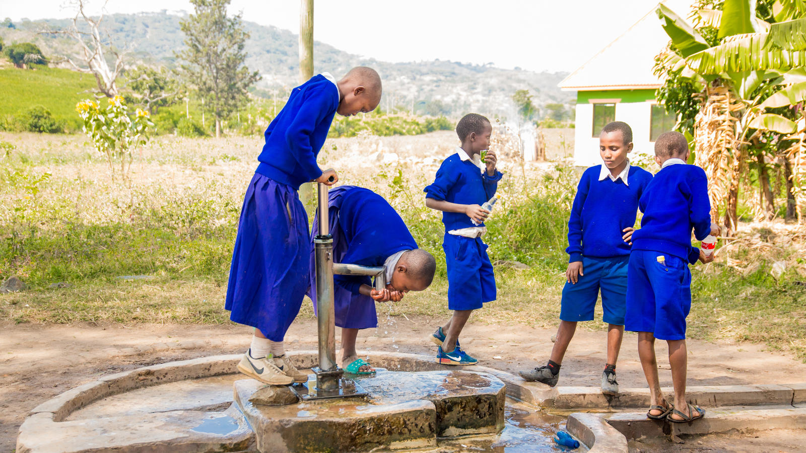 Children from a primary school in Sangara Village collect water for free from one of the existing handpumps.