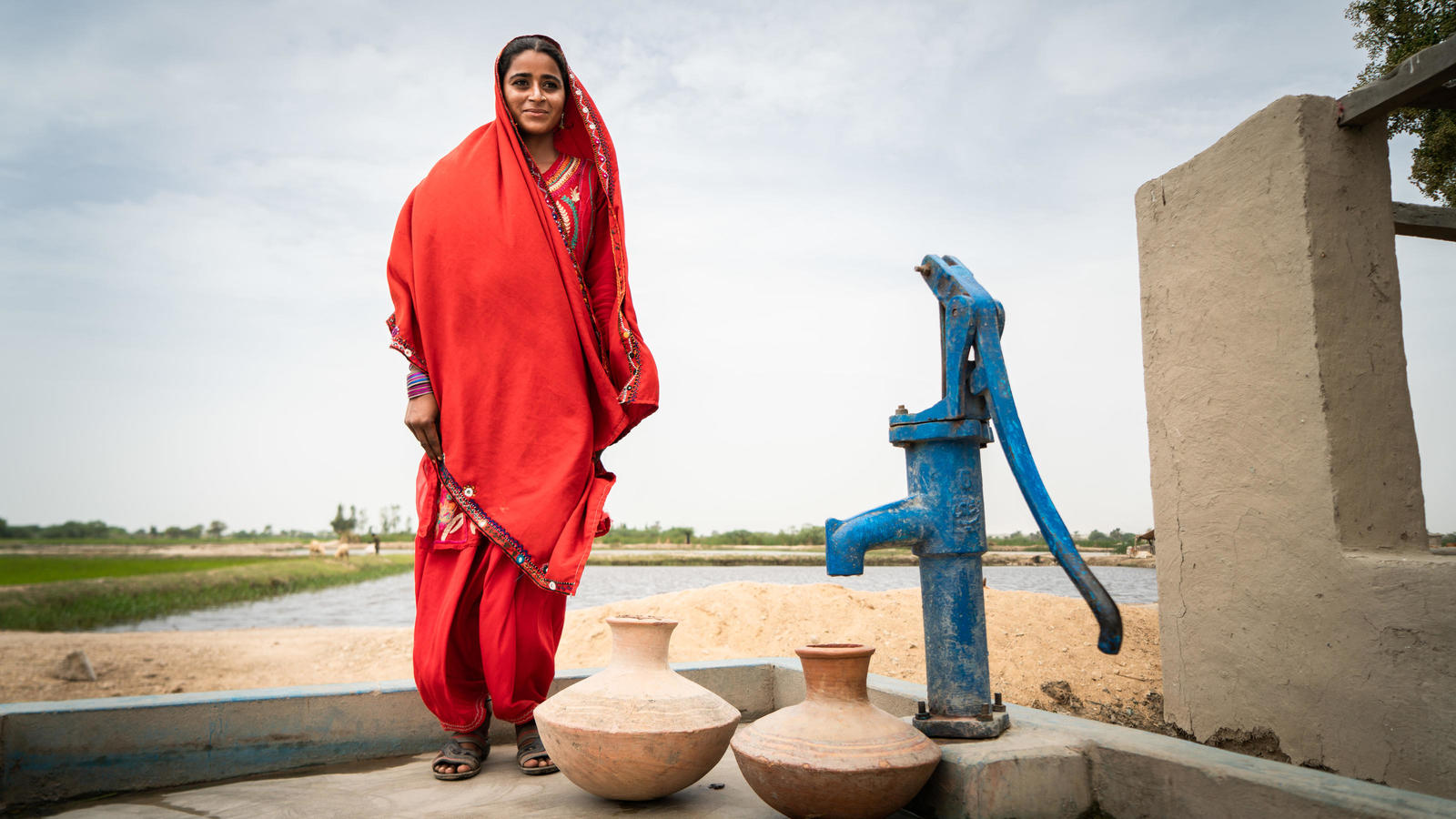 Sughra, 20, with a WaterAid installed water pump in the villlage of Muhammad Urs Sehejo, Chatto Chand Union Council, Thatta District, Sindh Province, Pakistan, September 2018.
