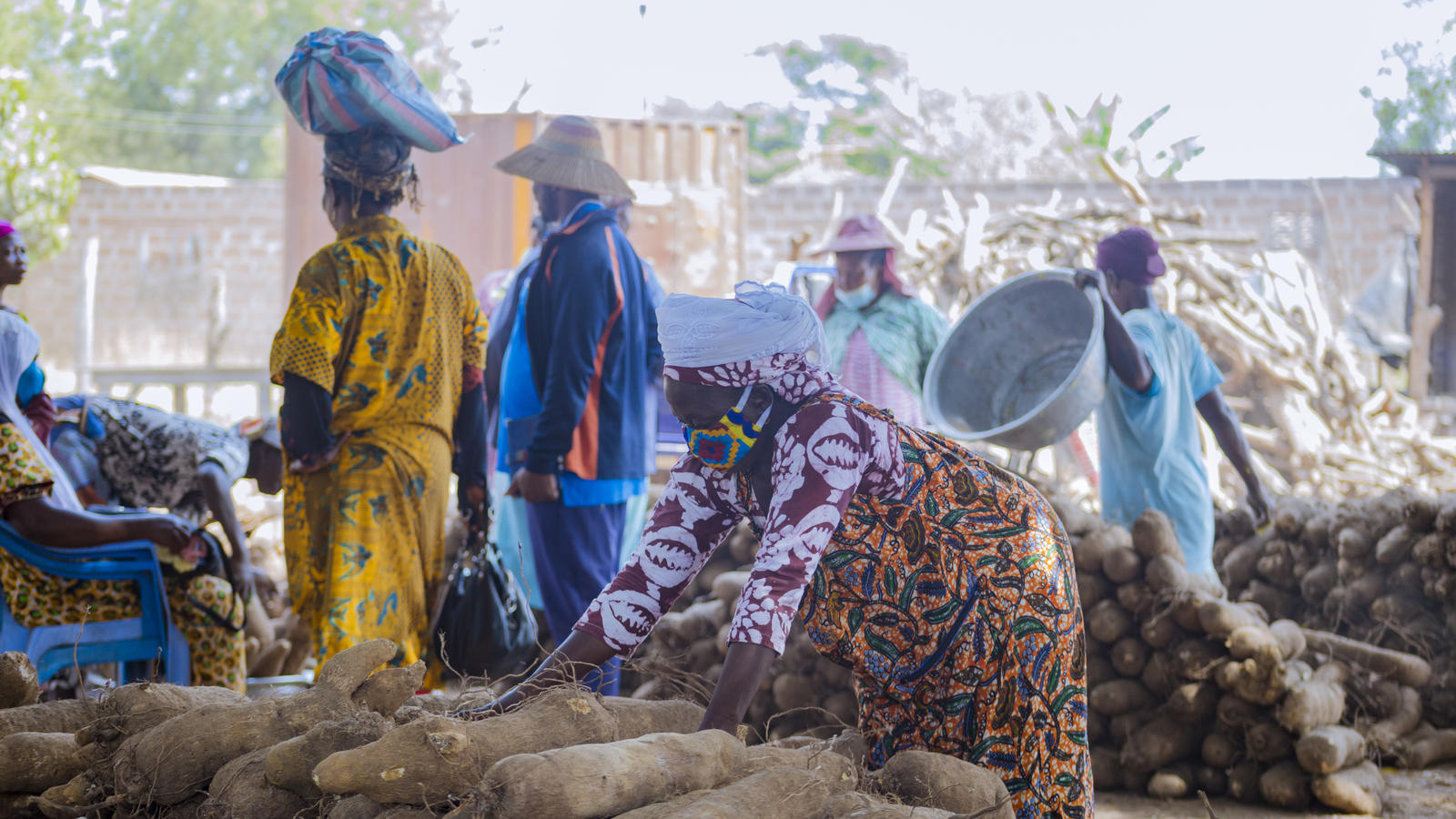 Women stack yams and carry produce at Bimbila Market in the Nanumba North Municipal Assembly, Ghana.