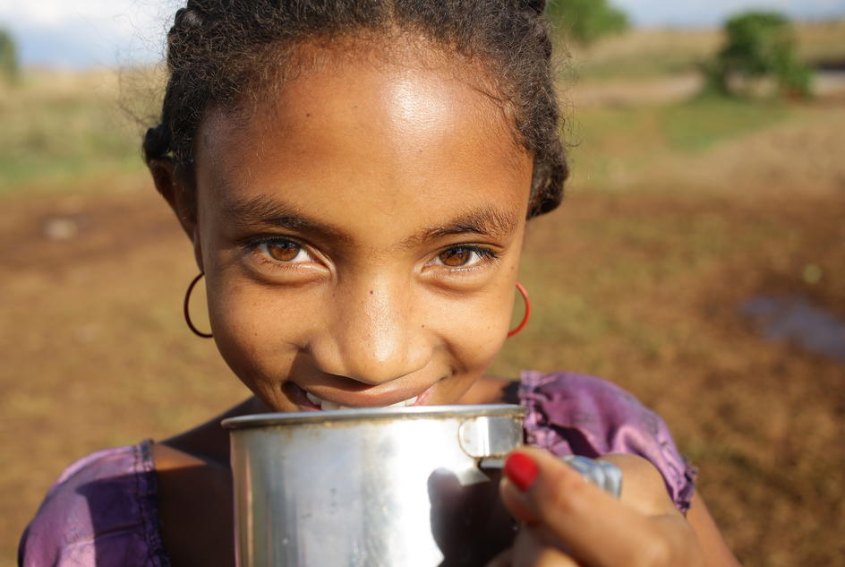 """Having enough water in our village makes us cleaner and less tired."" Aurelia drinking clean water at their temporary water point in Bongolava region, Madagascar."