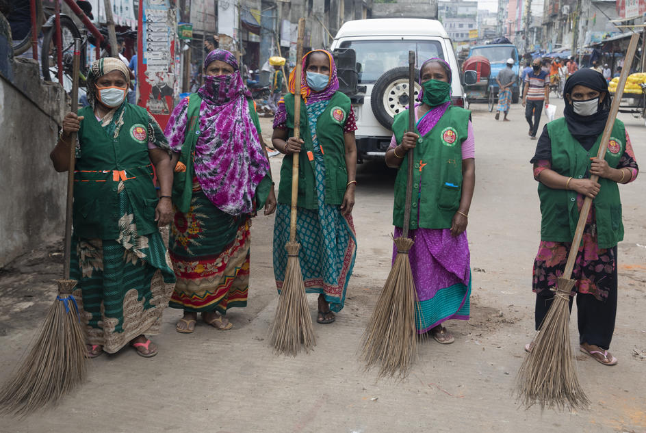 Five female road sweepers in Bangladesh standing with their brooms wearing face masks, during the COVID-19 pandemic in Bangladesh.
