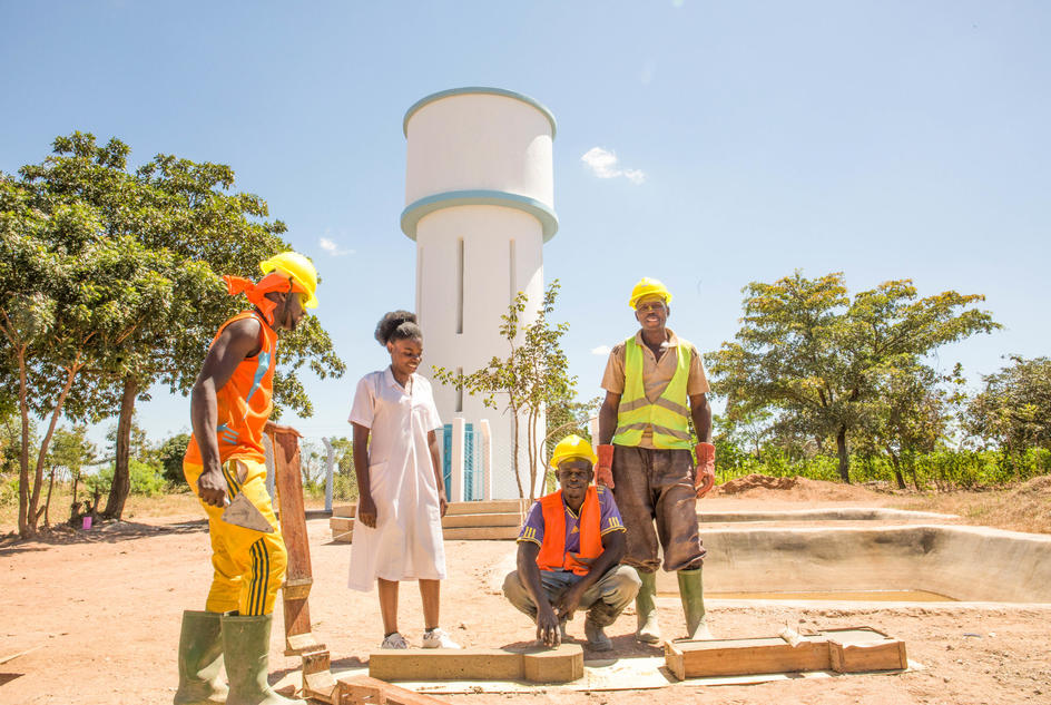 Grace, a nurse, talks to masons making final touches on newly installed water tank reservoir that will supply Kakora Dispensary with water all the time, Nyanghwale District, Tanzania.