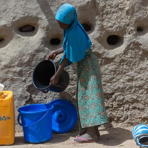 Malika, pours water into a bucket in Tillabéri, Niger,