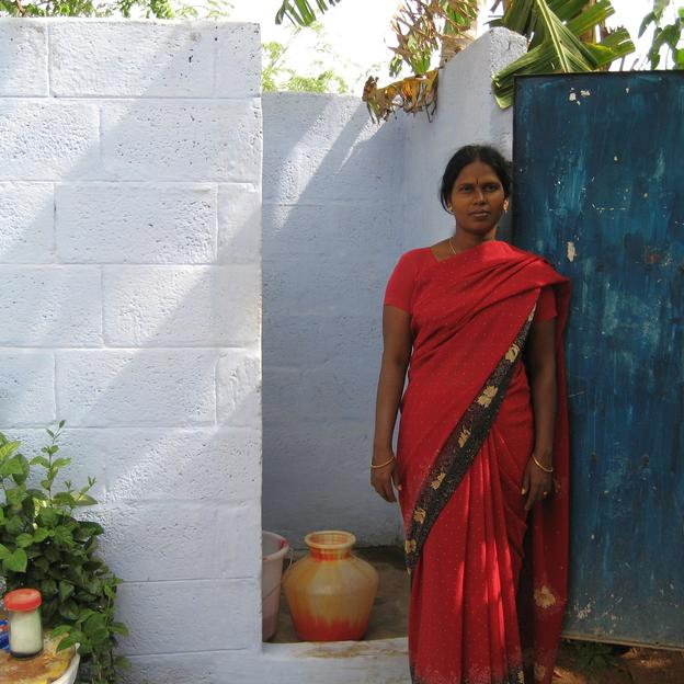 A woman standing in front of a toilet.