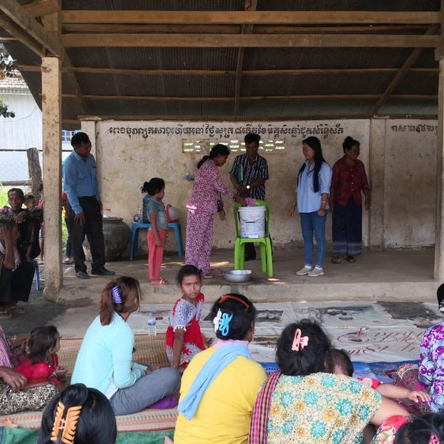 A group of people gather for a community hygiene promotion session in Kampong Speu Province, Cambodia.