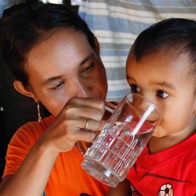 A mother feeds safe drinking water to her child