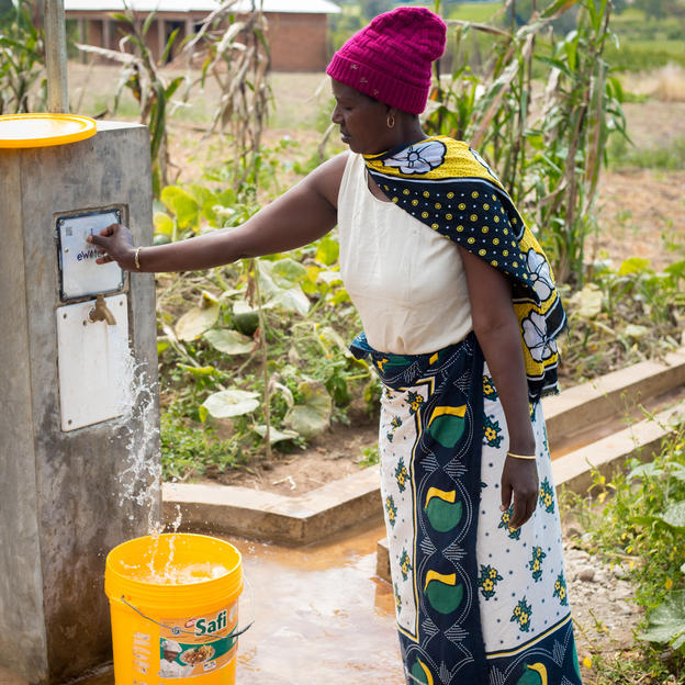 Community member Asha Kimoro uses her eWater token to collect water from a new distribution point, which is part of the WaterAid project. Sangara Village, Tanzania.