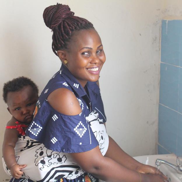 Community nurse, Francisca Edwin, with her baby using the new hand washing station at the Bandunu healthcare facility.
