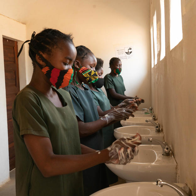 Melody, 13, and other female pupils washing their hands with soap at the sinks in the toilet block, Simango School, Kazungula District, Zambia, October 2020.