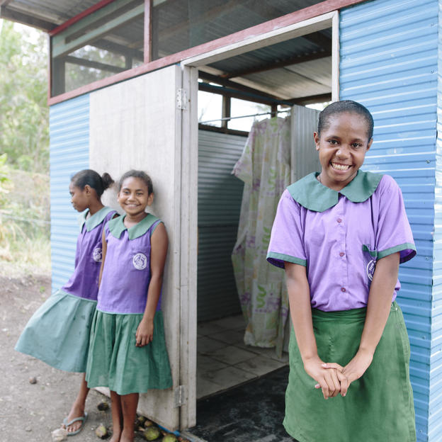 (Right) Jemima, 12, student in Grade 6, outside the girls toilet with friends (M-L) Bonni and Chanel at Ginigolo-Gunugau Primary School, Rigo District, Papua New Guinea. October 2018.
