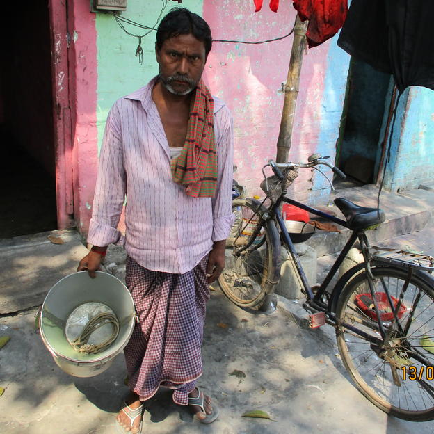 Sajib returning from a manual pit emptying job with bucket, spade and bicycle (pseudonym used to protect anonymity).