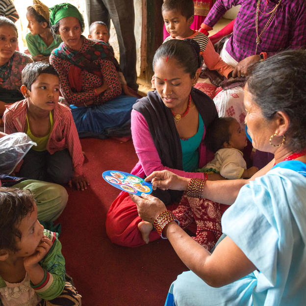 Swala Kumari Singh (right) shows a fan displaying five key hygiene behaviours to Chandra Malla (black shawl) during a hygiene session in Jajarkot, Nepal.
