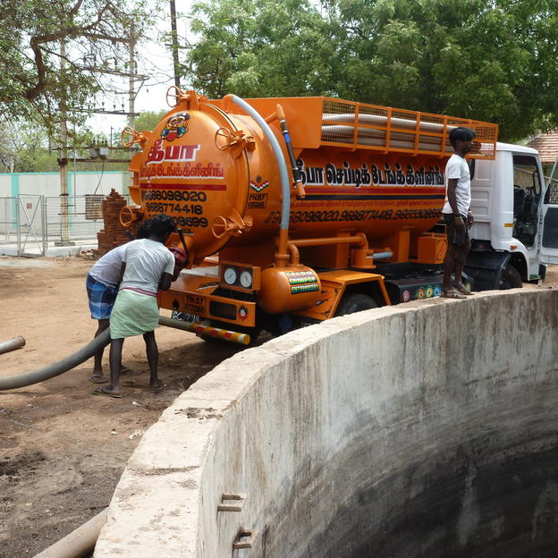 Three men preparing to discharge a vacuum tanker into a pumping station sump in Tiruchirappalli, India.