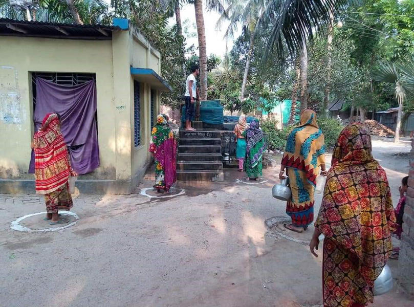 Women queue to collect water, maintaining social distance, in Bangladesh.